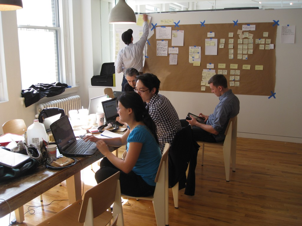 Picture of team at table, with sketchboard on wall